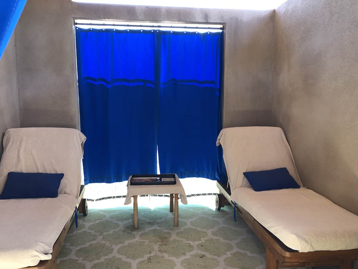padded lounge chairs and table in pool cabana