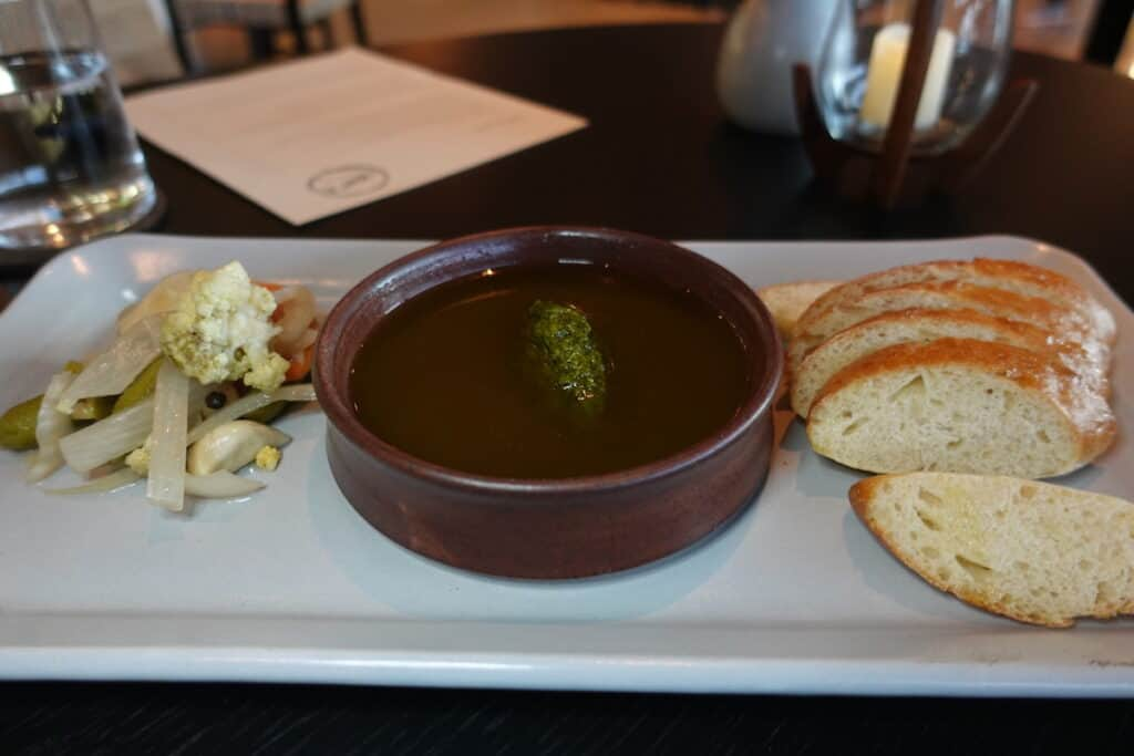 olive oil based dip with slices of sourdough bread and picked vegetables