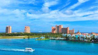 white boat on water near city buildings Atlantis Bahamas