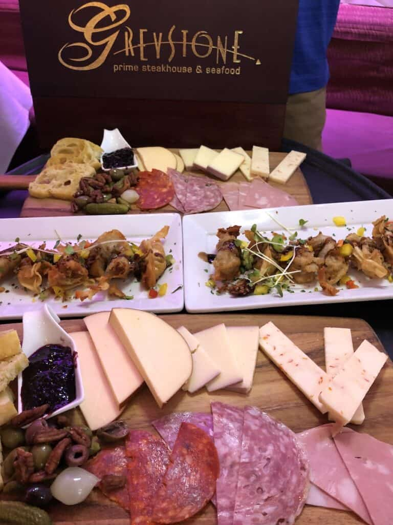 sliced meats and cheeses on wood board, charcuterie, greystone steakhouse