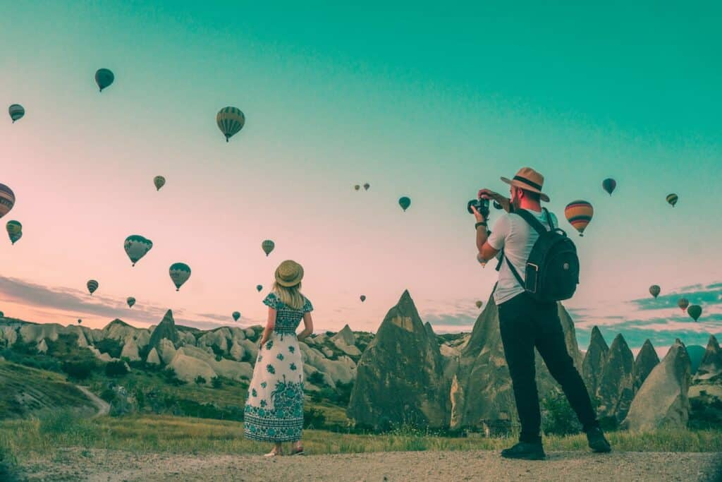 man taking photo of hot air balloons and blonde woman in maxi dress wearing a straw hat
