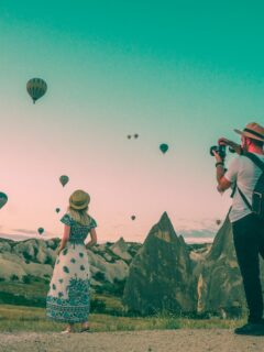man taking photo of hot air balloons and blonde woman wearing maxi dress and straw hat in cappadocia