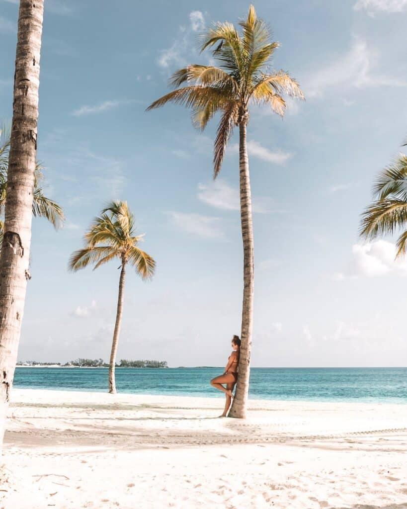 woman leaning on tree near beach, nassau bahamas caribean