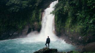 man standing on cliff near falls