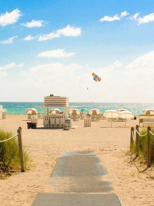 gray pathway leading to parasailing on beach in Miami
