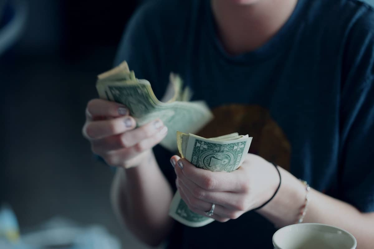 caucasian person in blue shirt with silver nail polish counting dollar bills