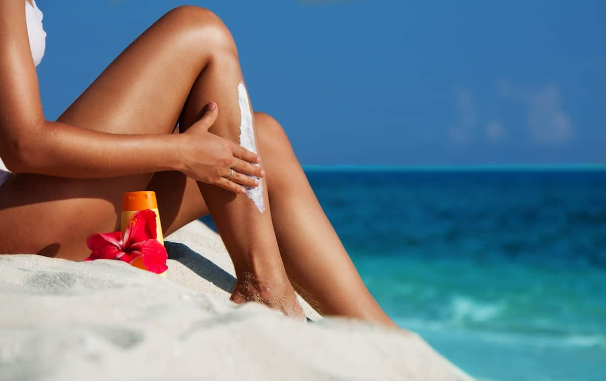 Tanned woman in white bikini sitting on a white sand beach putting sunscreen on her leg