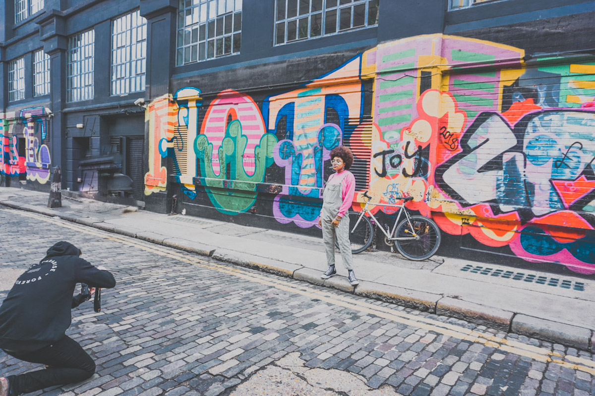 photographer dressed in black taking photo of girl in front of street art in Shoreditch London