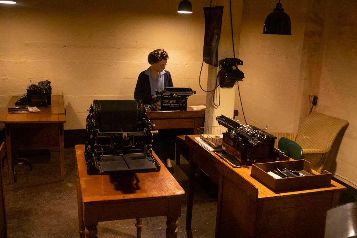wax figure secretary at typewriter and multiple typewriters in Churchill War Rooms