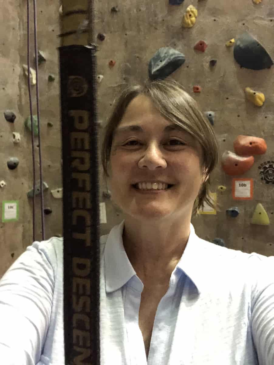 brunette woman in light colored shirt in front of an indoor rock climbing wall