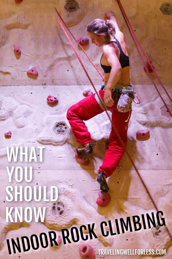 young woman in black sports bra and red pants climbing an indoor rock wall