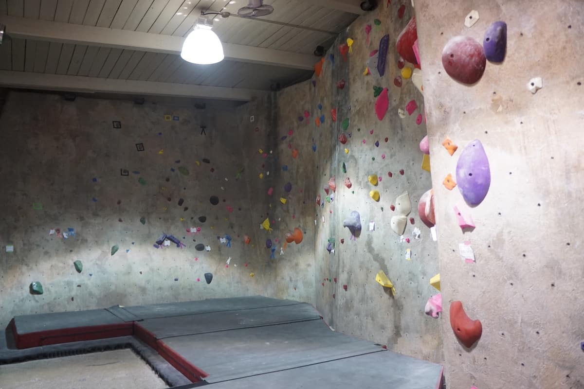 low indoor rock climbing wall with thick pads on floor