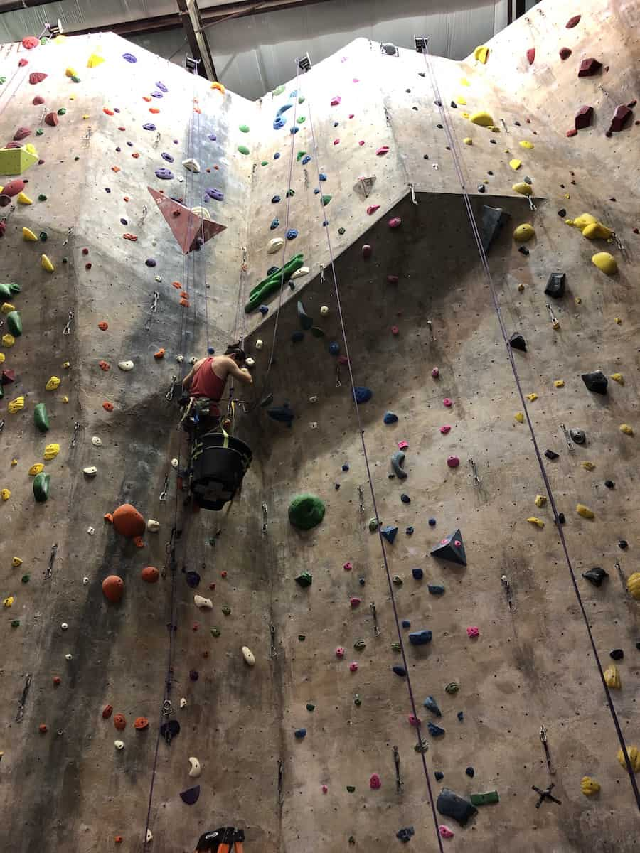 man harnessed into indoor rock climbing wall with a green bucket of hand and food holds