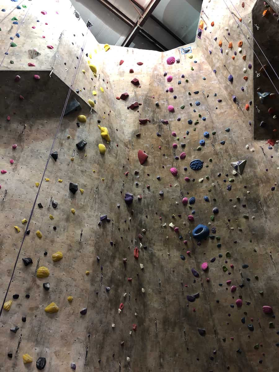 tall indoor rock climbing wall with various size and colored hand and foot holds