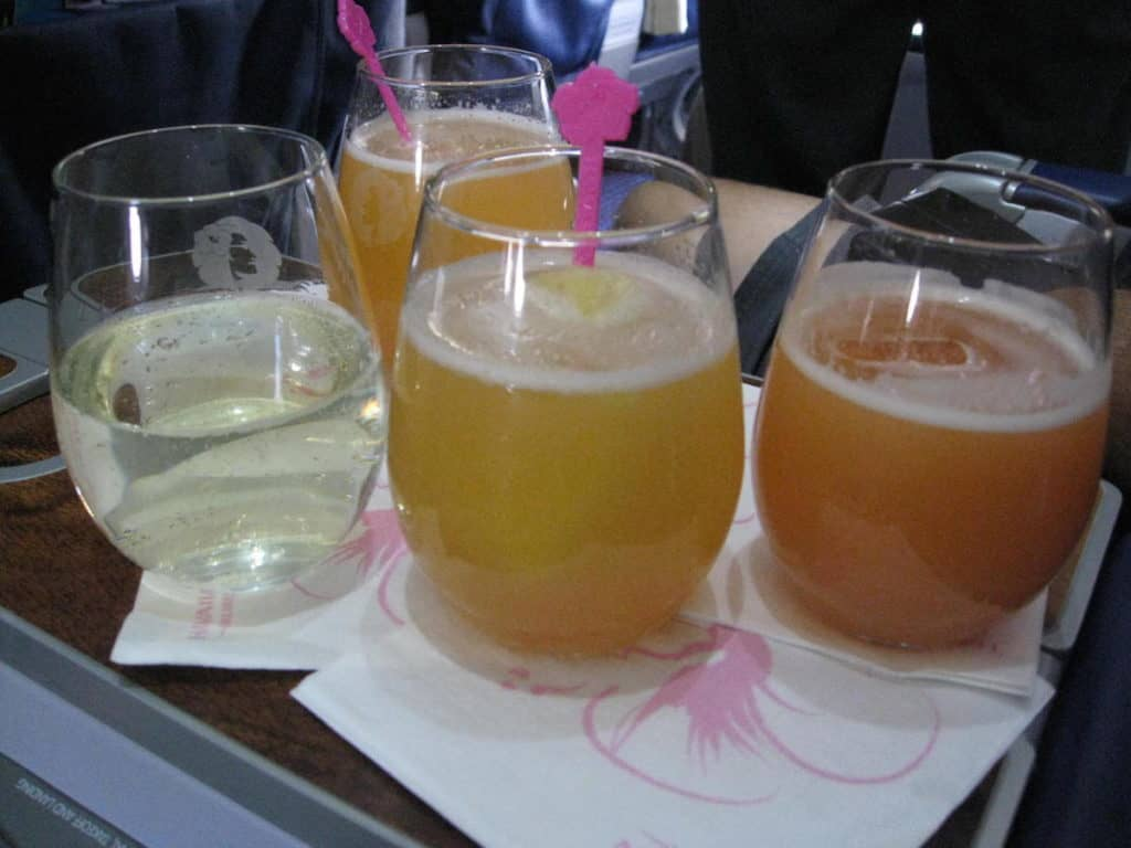 Hawaiian Airlines pre-departures drinks: Na Pua (guava juice and champagne), champagne, and guava juice. Traveling Well For Less